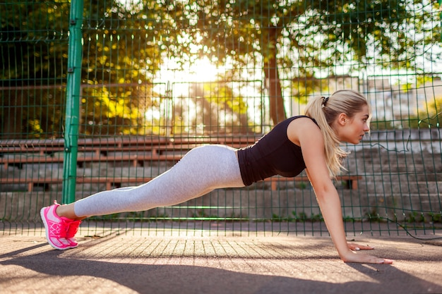 Young woman athlete doing push-ups on sportsground