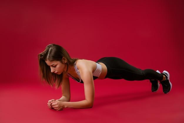 젊은 여자 선수는 피트니스에 종사하고있다. 운동 개념