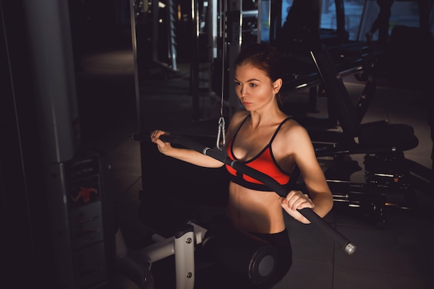 Young woman athlete pulls on at gym