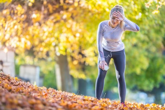 아름 다운 화려한 가을 공원에서 실행 한 후 젊은 여자 운동 선수 주자 피곤 호흡.