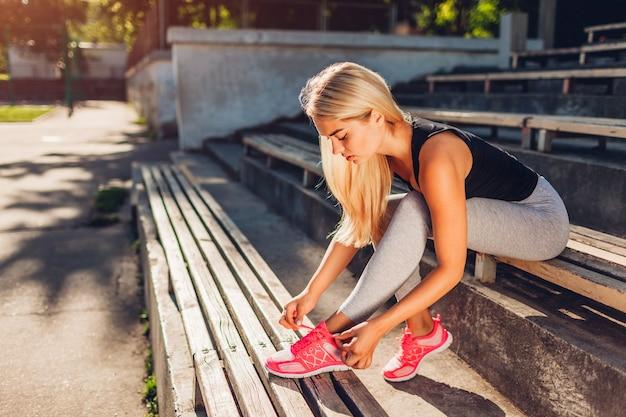 여름에 운동장 벤치에 앉아 운동화를 묶는 젊은 여성 운동선수. 훈련을 위한 준비. 운동하다