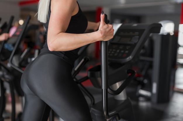 아름다운 섹시한 몸매를 가진 젊은 여자 선수는 체육관에서 현대 시뮬레이터에 종사하고 있습니다