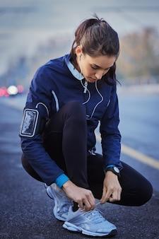 Молодая женщина-спортсмен с наушниками слушает музыку и завязывает шнурки на улице