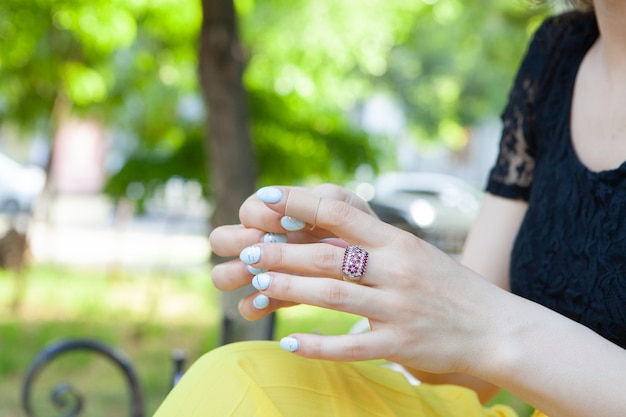 젊은 여자는 공원에서 그녀의 손가락에 석고를 부착