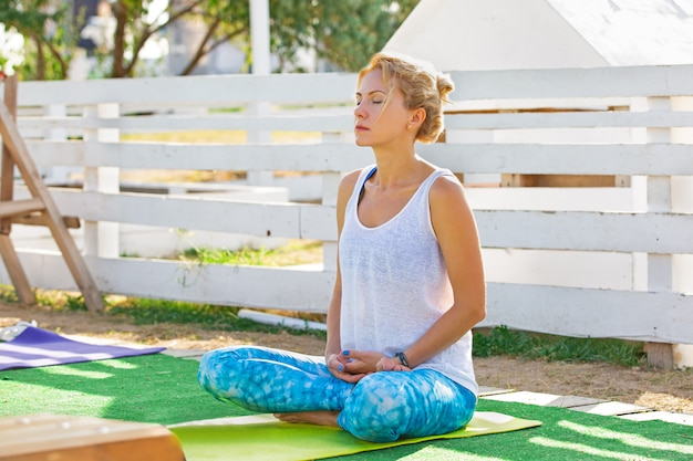 Young woman attending a yoga class outside in park