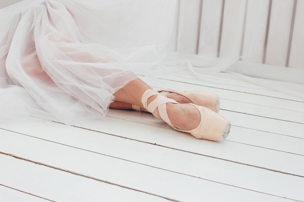 Young woman authentic ballerina ballet dancer in pointe shous sitting on white floor