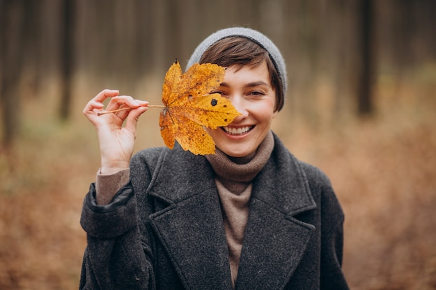 Young woman in autumn park holding leaf by the face