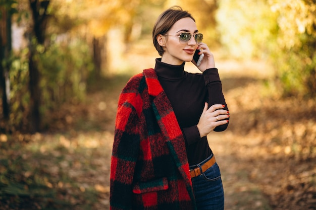 Young woman in autumn park using phone