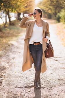 Giovane donna nel parco d'autunno