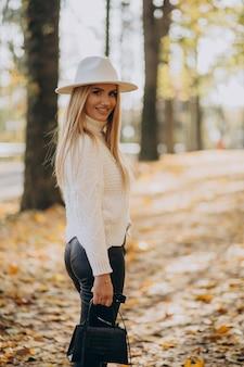 Giovane donna in un parco in autunno