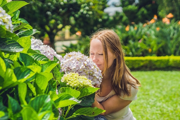 Young woman on the background of light pink hydrangea blooming in the garden