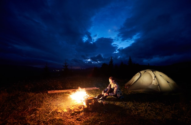 Young woman backpacker enjoying at night camping in the mountains, sitting near burning campfire and illuminated tourist tent under beautiful evening cloudy sky. tourism, outdoor activity concept