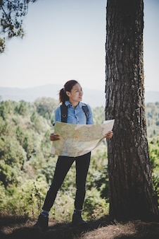 Young woman backpacker hiker reading map hiking trip. relaxing on holiday.