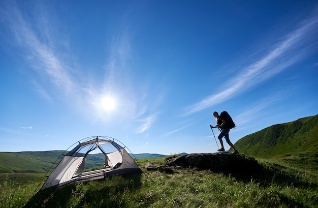 Young woman backpacker with backpack and trekking sticks climbing up on big stone on the top of a hill near tent against blue sky, sun and clouds, in the mountains. camping lifestyle concept