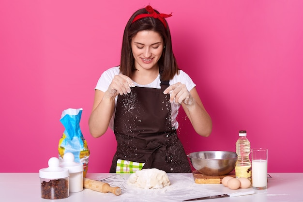 Young woman baker in kitchen, sprinkling white flour on dough, baking delicious coockies, likes homemade pastry, posing isolated on pink. copy space for your advertismant or promotion.