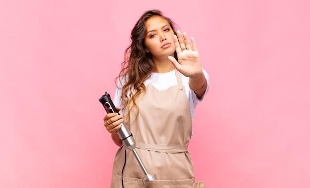 Молодая женщина-пекарь выглядит серьезной, строгой, недовольной и сердитой, показывая открытую ладонь, делая стоп-жест