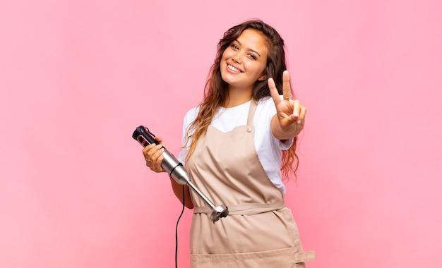 젊은 여자 베이커 미소하고 행복하고 평온하고 긍정적 인, 승리 또는 평화를 한 손으로 몸짓
