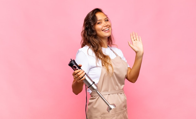 若い女性のパン屋は、楽しく元気に笑ったり、手を振ったり、歓迎して挨拶したり、さようならを言ったりします