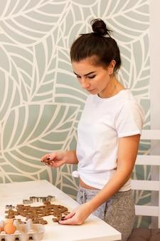 Молодая женщина печет пряники на кухне