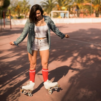 젊은 여자 롤러 스케이트에 균형