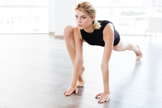Young woman ballerina stretching legs in dance class