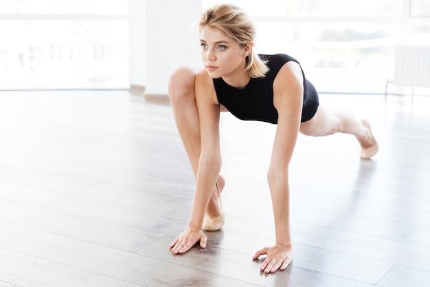 Молодая женщина балерина растягивает ноги в танцевальном классе