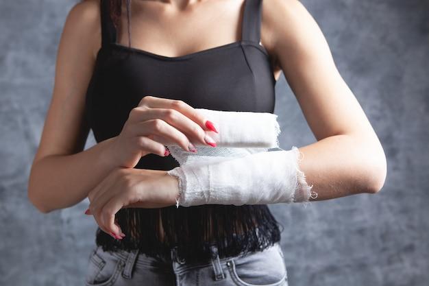 젊은 여자는 그녀의 손을 붕대