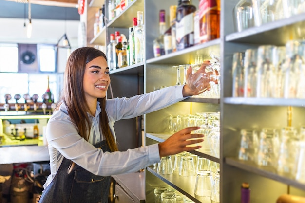 Young woman behind bar taking a clean glass to pour a drink.