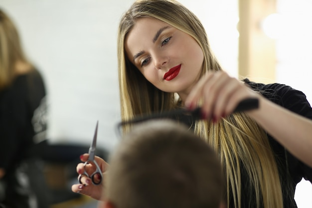 Young woman barber cutting client hair in salon. hairdresser holding scissors and hairbrush. beautiful hairstylist combing man.