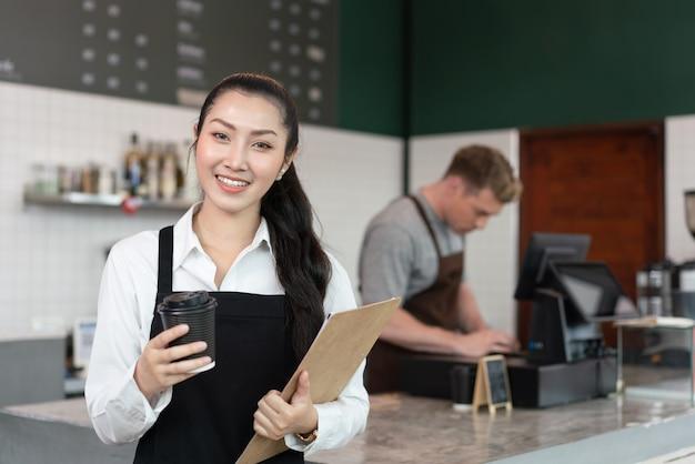 커피숍에서 커피 한 잔을 들고 웃고 있는 젊은 여성 바리스타 커피숍 주인