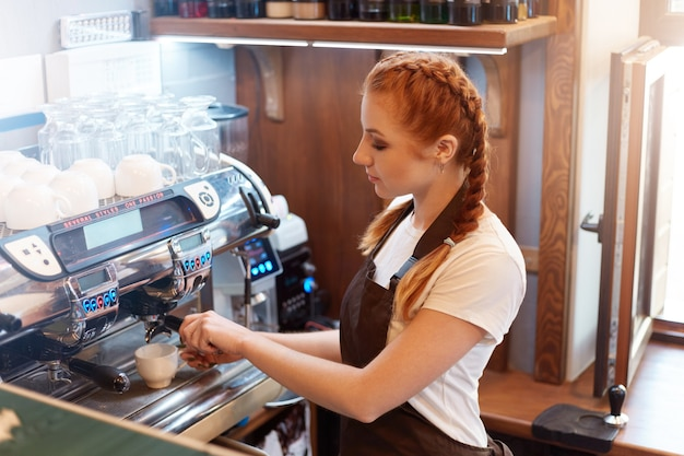 Молодая женщина-бариста готовит кофе с помощью машины в кафе
