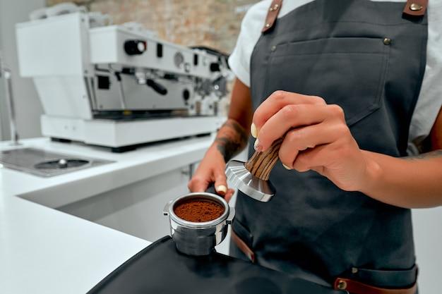 Молодая женщина-бариста прессует молотый кофе, используя трамбовку в кафе.