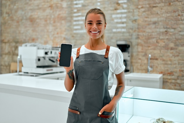 Young woman barista stands at the counter in a coffee shop and smiles while showing a blank smartphone screen.