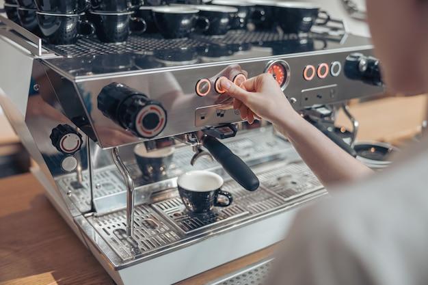Молодая женщина-бариста с помощью современной кофемашины в кафетерии