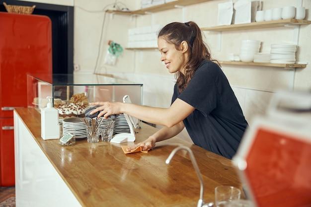 서서 커피 숍에서 바 카운터를 청소하고 카운터를 소독하는 젊은 여성 바리 스타.
