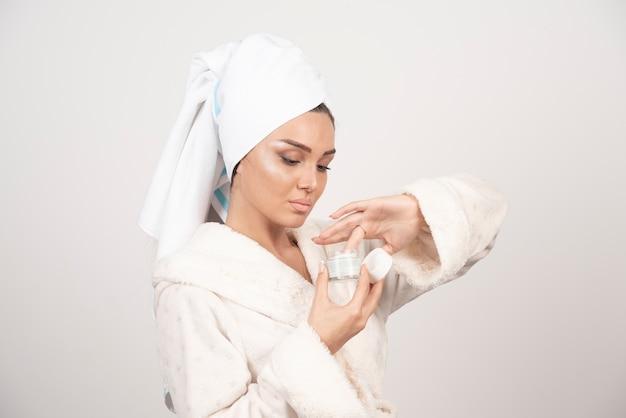 Giovane donna in un accappatoio che applica una crema