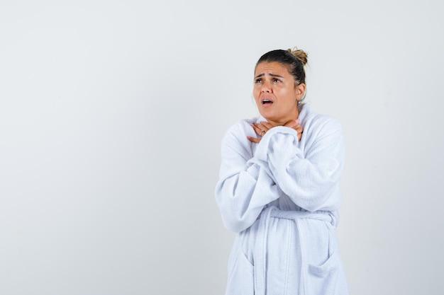 Giovane donna in accappatoio che si soffoca e sembra impotente