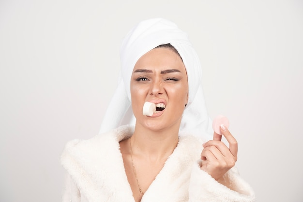 Young woman in a bathrobe doing make-up .