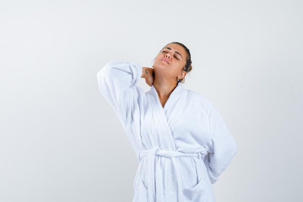 Young woman in bathrobe holding hand on neck and looking unwell