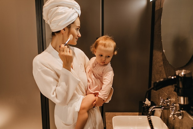Young woman in bathrobe holds blonde daughter and does her own makeup, looking in bathroom mirror.