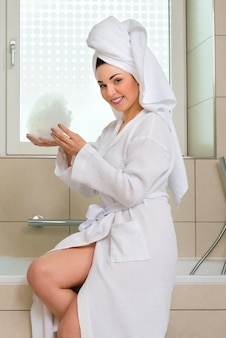 Young woman in bathrobe in hotel bathroom