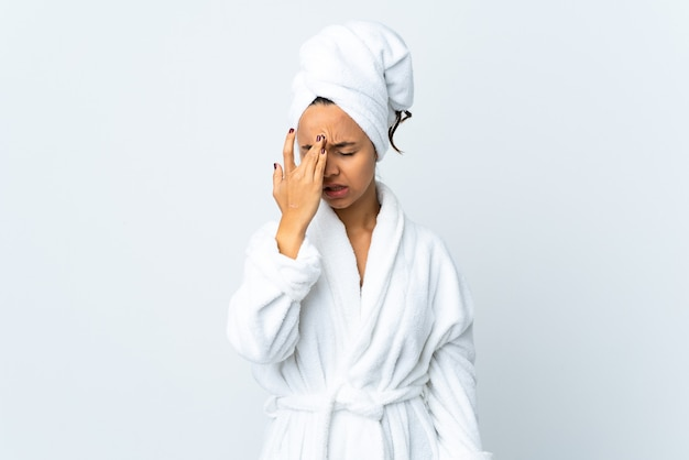 Young woman in bathrobe over isolated white background with headache