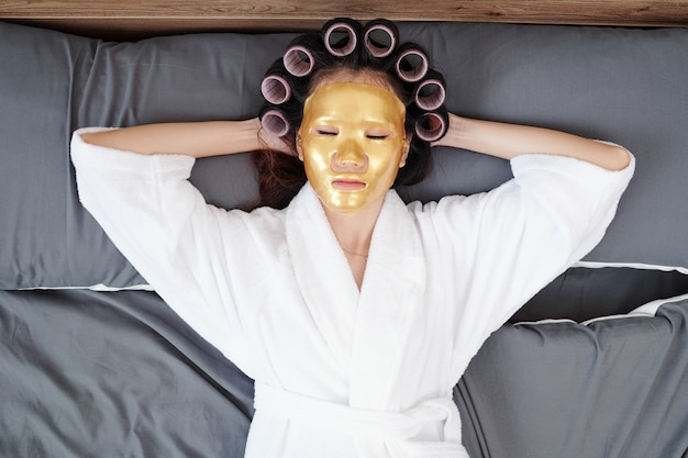 Young woman in bathrobe relaxing on bed with hair rollers and sheet mask on, view from the top