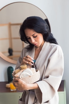 Young woman in bathrobe with body care products basket