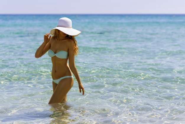 Young woman at the beach. portrait of a girl in white hat having fun in the sea