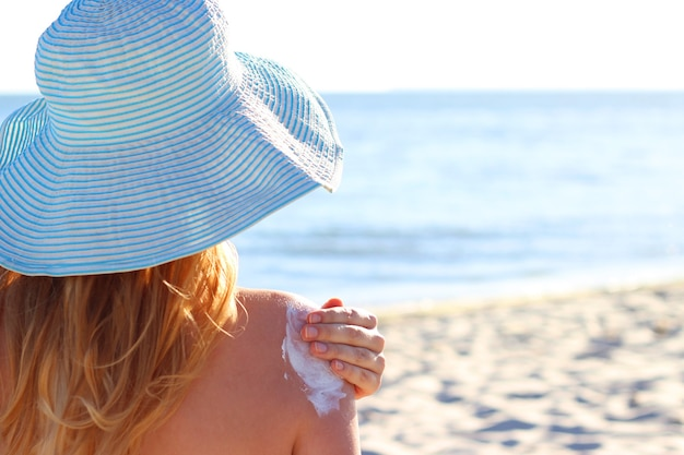 Young woman on the beach uses sunscreen