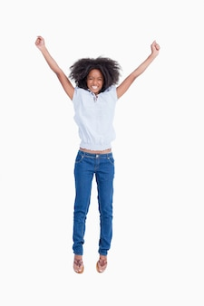 Young woman beaming while raising her arms above the head