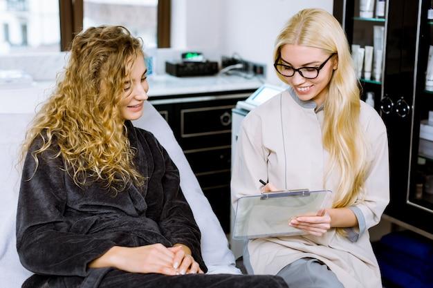 現代の美容センターで新しい顔のスキンケアの手順について若い金髪の巻き毛の女性と話している若い女性美容師