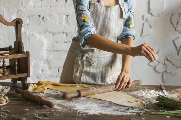 Young woman in beautiful dress and apron preparing dough for homemade pasta at rustic kitc