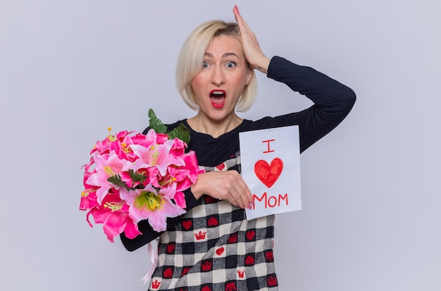 Young woman in beautiful dress holding greeting card and bouquet of flowers looking at front surprised with hand on her head celebrating mother's day standing over white wall